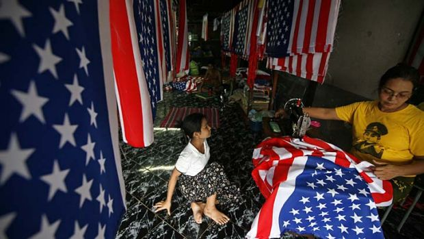 Waving the flag ... a woman in Rangoon sews US flags in preparation for President Obama's visit.