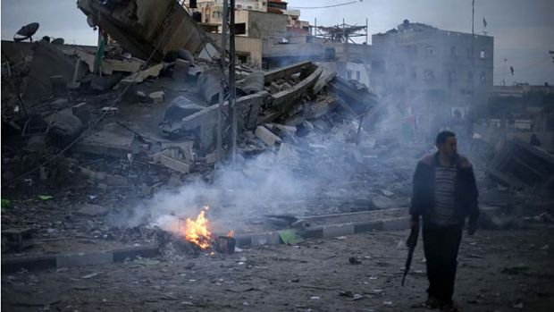 Conflict ... a Hamas police officer at the destroyed headquarters of Gaza's Prime Minister.