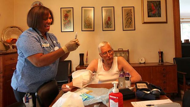 Home support ... nurse Cynthia Holbeck attends to patient Don Auchterloni in his home.