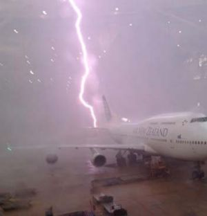 Near miss ... a lightning strike just misses a plane at Brisbane airport.