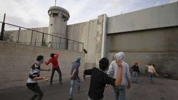 Anger ... Palestinian youths in Bethlehem attack the Israeli security wall with stones on Saturday.