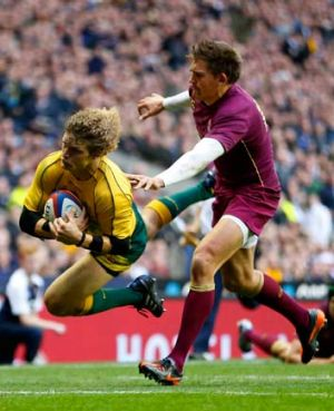 Slippery ... Wallabies winger Nick Cummins eludes Toby Flood of England to score a try at Twickenham on Saturday.