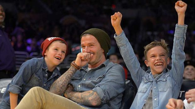 What's so funny? … David Beckham shares a laugh with sons Cruz and Romeo at a Los Angeles Lakers game on Friday.