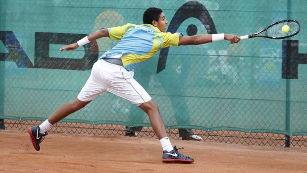 Canberra Velocity's Nick Kyrgios slides across the clay to reach a backhand.