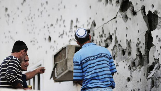 Residents in Okafim, southern Israel, inspect the damage from a rocket fired from Gaza.