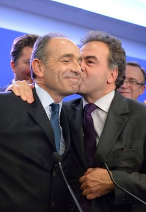 Jean-Francois Cope is congratulated by campaign team member Luc Chatel after the announcement of his victory in the UMP ...