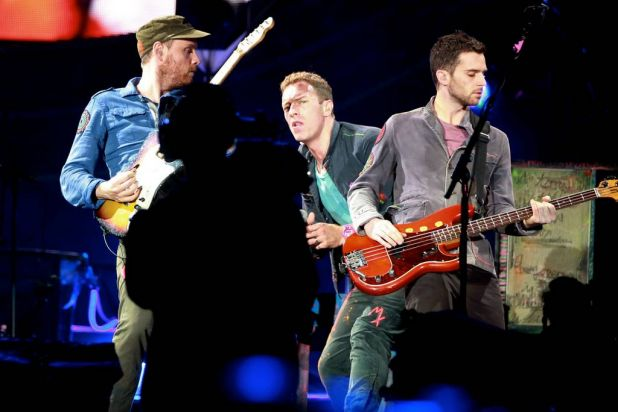 Jonny Buckland on guitar, singer Chris Martin and Guy Berryman on bass guitar.