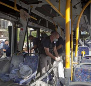 Aftermath ... Police officers examine the destroyed bus at the site of the bombing in Tel Aviv.