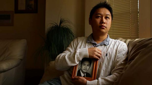 A worried Tommy Du holds a picture of his father, jailed in China.