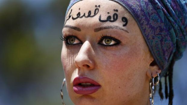 "Renee Jan from Gilmore with ""stop bombing Gaza"" written in Arabic on her forehead during a Rally for Palestine rights."