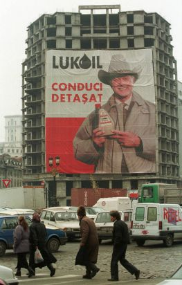 Romanians cross the street by an unfinished apartment building draped with a poster representing US actor Larry Hagman ...