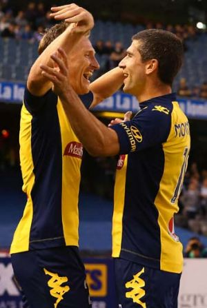 On target: Mariners striker Daniel McBreen (left) celebrates a goal against Melbourne Victory.