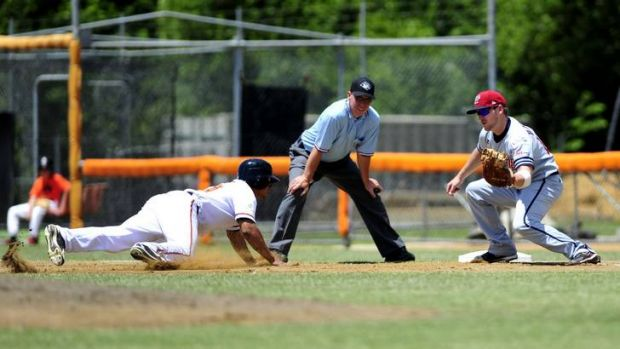 Canberra's Jonathan Jones slides back to first base as Brad Harman waits for the ball.