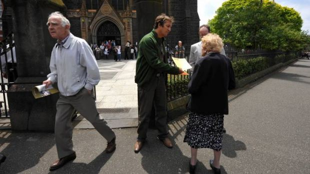 Hear this: Clergy abuse activist Mark Fabbro hands out flyers outside Melbourne's St Patrick's Cathedral.