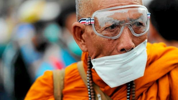 Protests … a Buddhist monk wears a mask as a protection against tear gas.