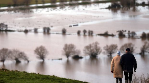 Water everywhere ... people walk from Glastonbury Tor above flooded fields, on Sunday in Somerset, England.