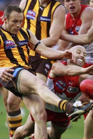 Sydney's co-captain Jarrad McVeigh attempts to smother the kick from Brad Sewell in the grand final.