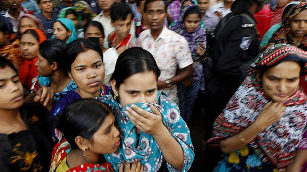 Anxious wait ... people gather outside the burnt garment factory outside Dhaka, Bangladesh, where more than 100 people ...
