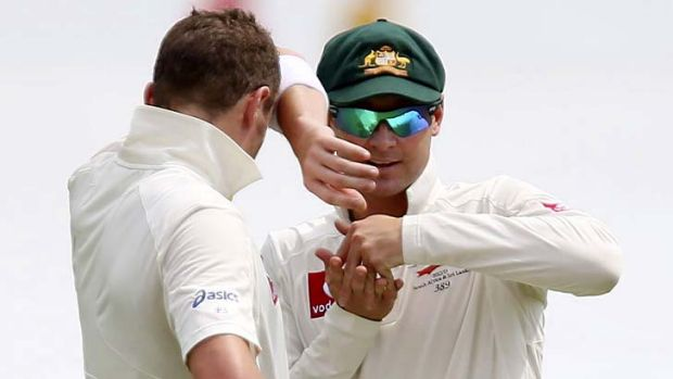 Australia's captain Michael Clarke plots with teammate Peter Siddle.