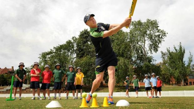 Brad Haddin helps Canberra Grammar students during a Milo Cricket training session.
