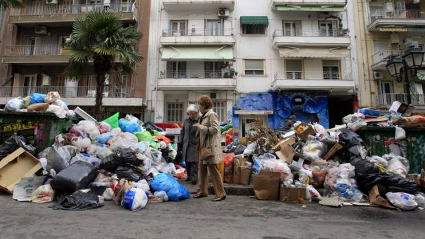 On the nose ... women navigate piles of rubbish in Thessaloniki after strikes by municipal workers over austerity measures.
