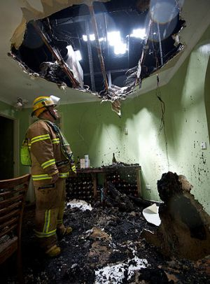 Incoming ... A firefighter stands under a hole blasted through the roof of a house in Berwick by a lightning strike.