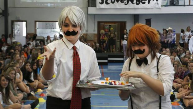 Merici College students Sarah Beaver and Bree Hall offer some lollies to the judges during the Movember Fashion Parade.