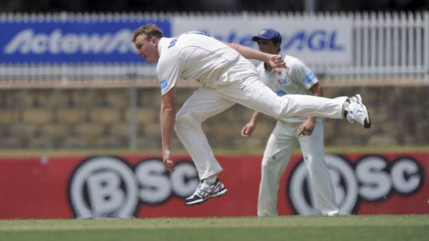 NSW bowler Doug Bollinger bends his back during the Sheffield Shield clash with Queensland at Manuka Oval.