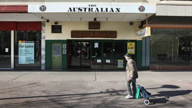 A man walks past closed businesses in Garema Place, Civic.