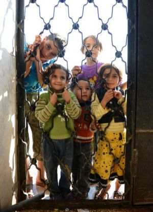 Displaced ... Syrian children wait for food at a school housing around 140 refugees in the village of Atme.