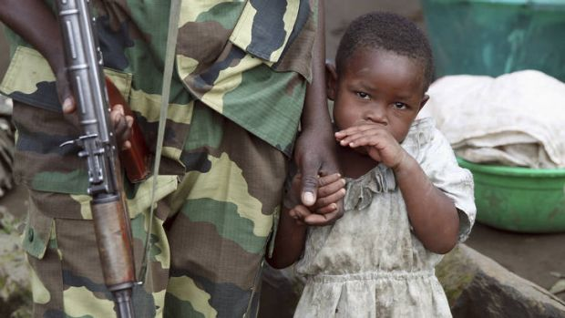 Divided ... a girl holds a hand of a M23 rebel fighter as the rebel groups prepare to withdraw from the town of Karuba, ...
