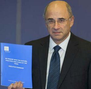 Lord Justice Leveson poses with a summary of the Leveson Report.