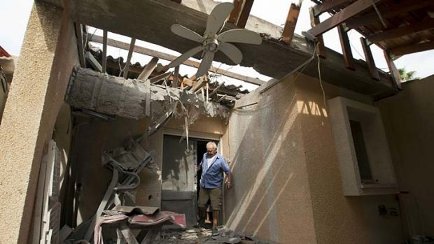 An Israeli man inspects the damage to his house following a rocket attack on the Israeli Kibbutz Ein Shlosha from the ...