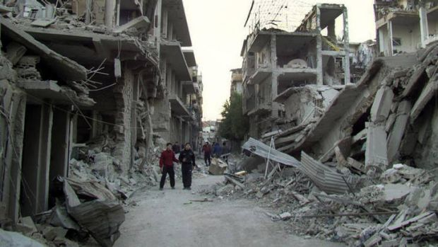 Rubble and ruin … Homs residents walk down a city street destroyed in missile strikes by Syrian warplanes this week.