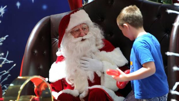Part-time Santa, at Westfield Belconnen, John Rundle, has his photo taken with eight-year-old Ryan Prichard of Gungahlin.