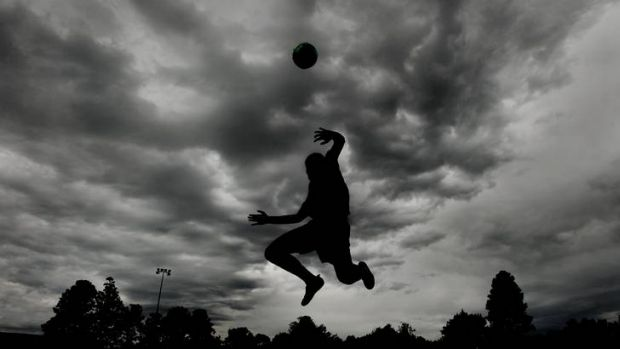 Jake Montgomery practising soccer as the dark clouds gather over Kingston Oval.