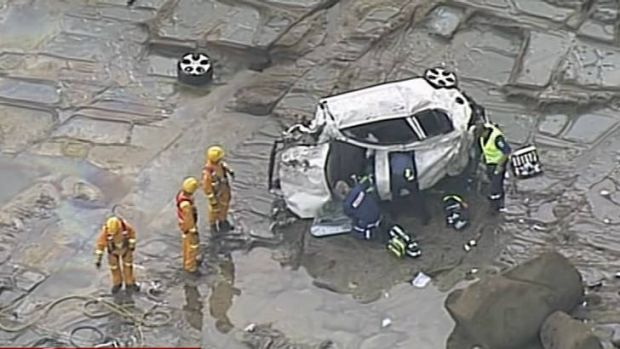 Rescue workers at the crash site near Apollo Bay work to free a woman trapped in her car at the base of the cliff.