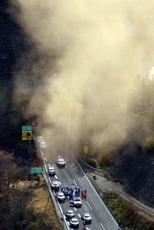 Fears of another cave-in ... smoke billows from the entrance of the collapsed Sasago tunnel.