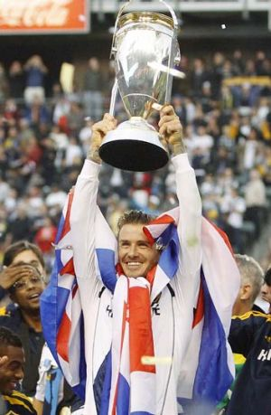 Los Angeles Galaxy's David Beckham holds the trophy after the Galaxy defeated the Houston Dynamo to win the MLS Cup ...
