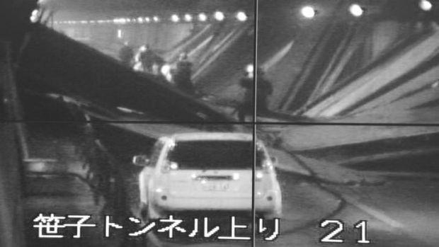 Salvage efforts ... a surveillance monitor shows a car and rescue team in the tunnel.