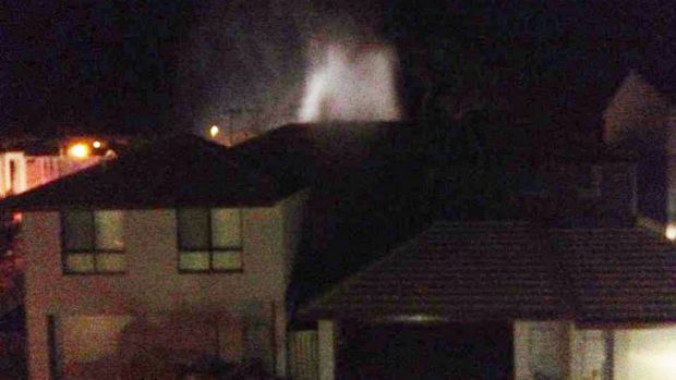 A water jet from the burst main could be seen above the roof tops of nearby houses. Photo supplied by Amy McEneny.