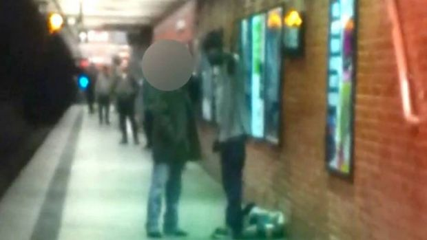 Photo anger ... two men are seen talking on a New York  subway platform before one was pushed in front of a train.