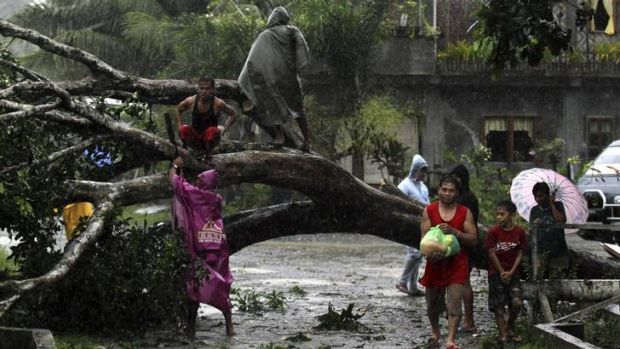 Residents try to clear the road near Tagum City.