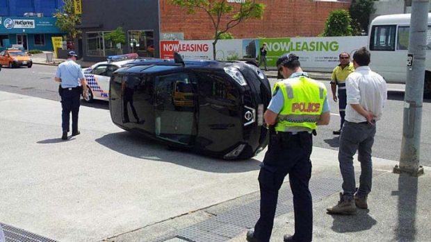 """A car sits on its side in Ann Street, Fortitude Valley, after a """"slight nudge"""" from another vehicle."""
