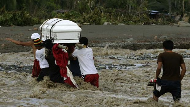 Wake of the storm ... relatives cross a river to bury a flood victim in the southern Philippines.