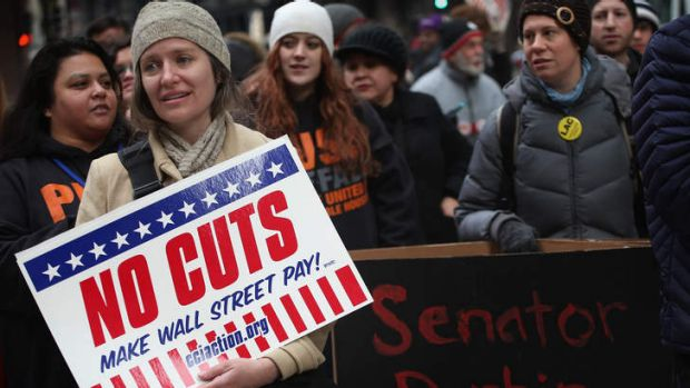 Protestors call for an increase of taxes on the wealthy and voice opposition to cuts in Social Security, Medicare, and ...