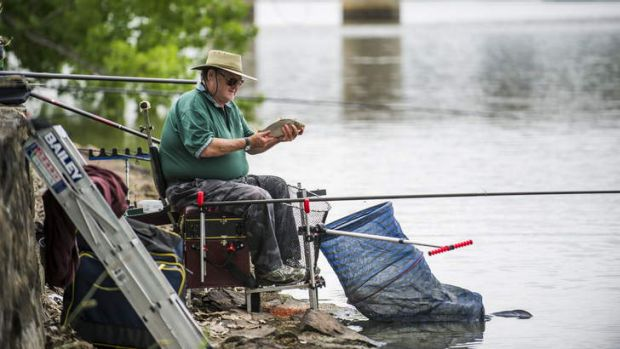 Howard Hill looks at a small carp he has just caught.