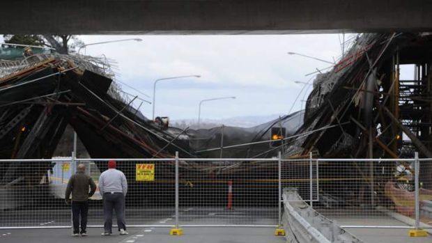 Locals investigate the scene of a bridge collapse on the Barton Highway.