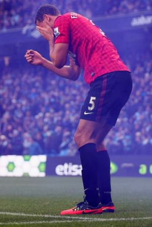 Rio Ferdinand reacts after being struck by an object thrown from the crowd during Sunday's derby.