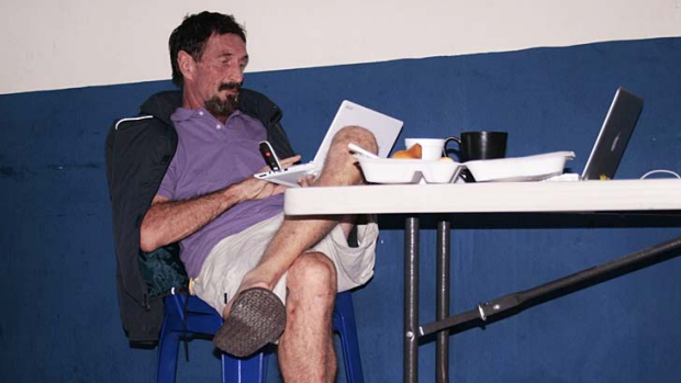 Caught on the run ... internet security pioneer John McAfee being interrogated by Interpol at police headquarters ...